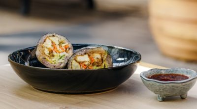 tofu sushi roll in bowl with sauce